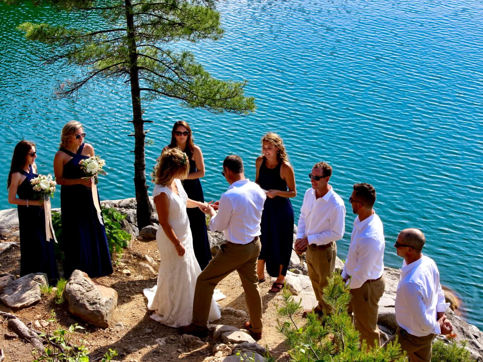 Bride and groom at their wedding ceremony overlooking exquisite Lake Topaz at Baie Fine Fjord.
