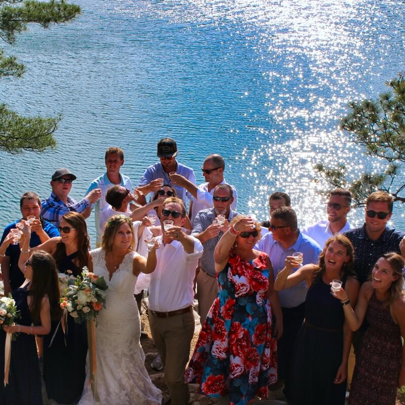 Wedding party enjoys a toast with Lake Topaz at Baie Fine Fjord as the backdrop.