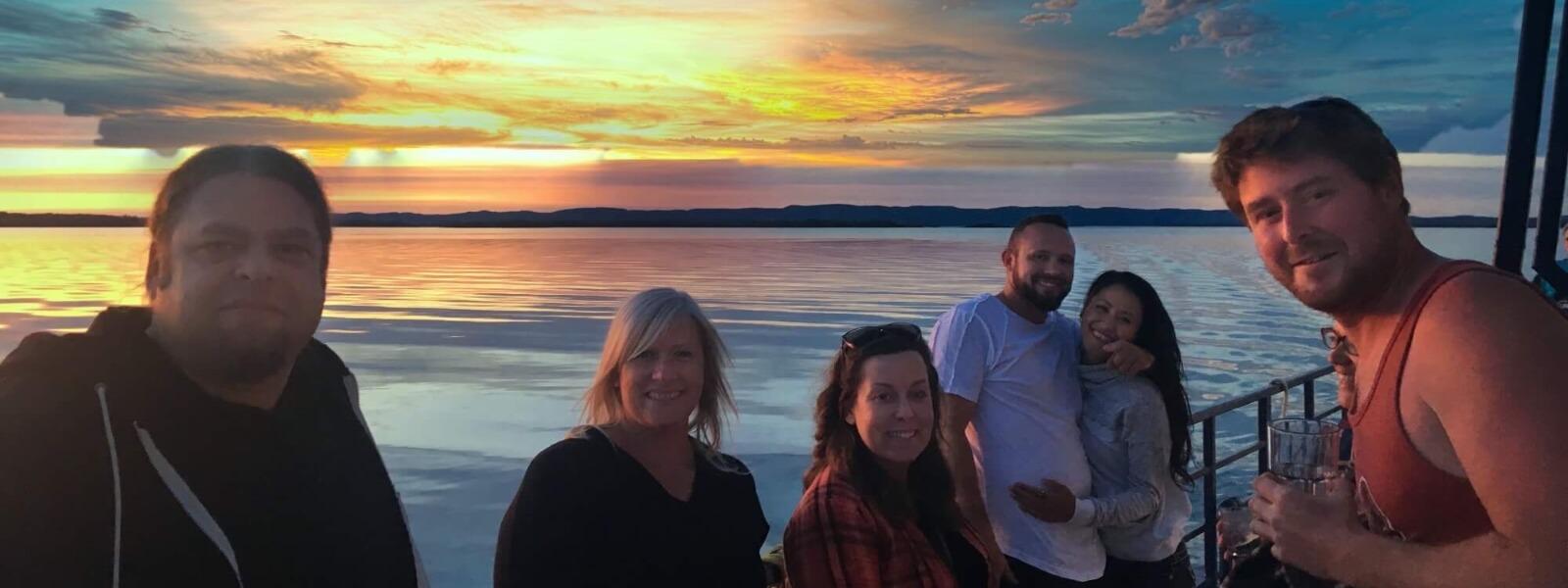 Passengers of a sunset dinner cruise enjoying a beautiful evening on the water.