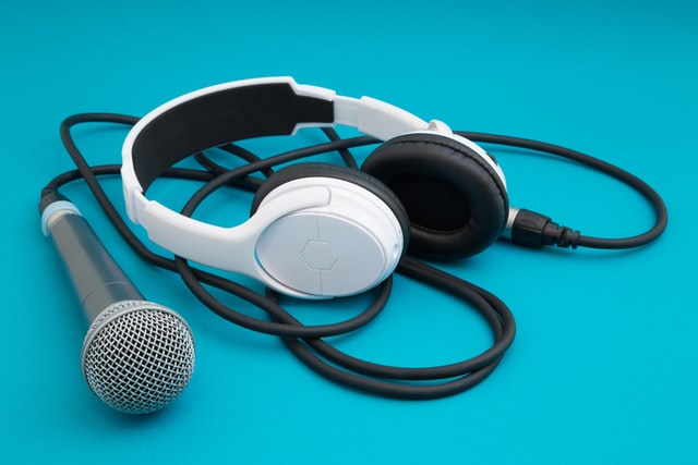 Headphones and microphone on blue background