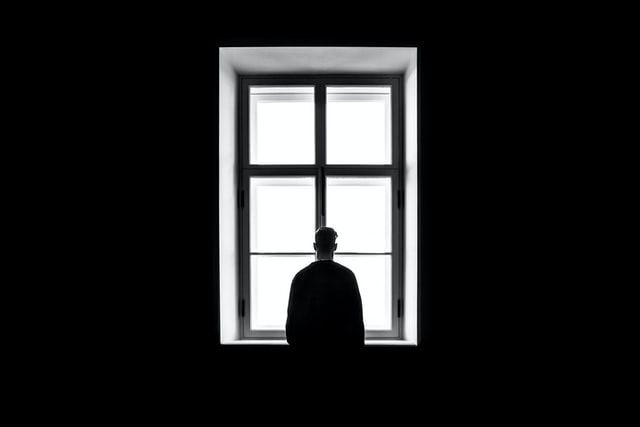 black-and-white image of man in dark room staring out white window and dealing with severe depression