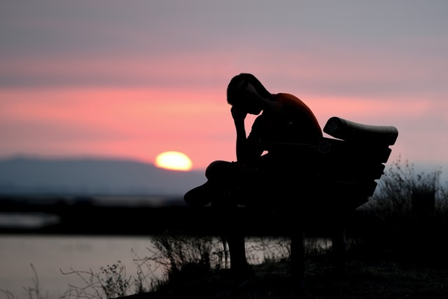 """man sitting on park bench in front of lake, wondering """"why am I so depressed?"""""""