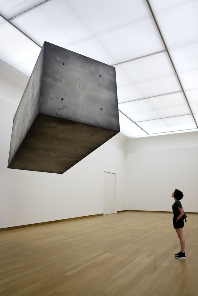woman in museum thinking outside the box while staring at huge floating box