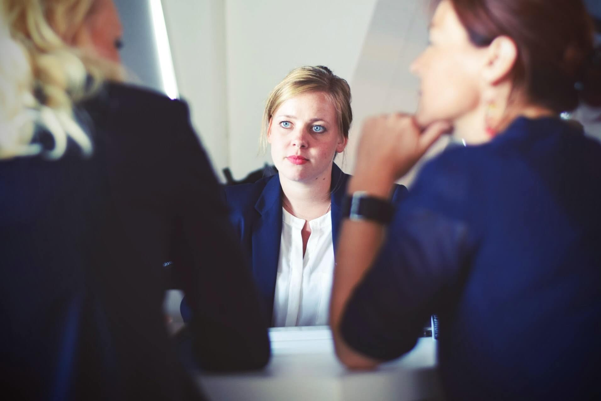 three women in business clothes talking about feeling stuck