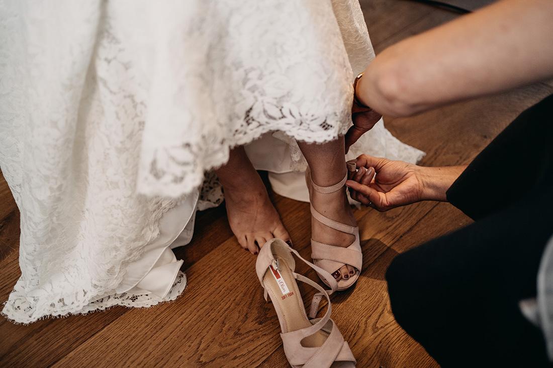Bruid krijgt assistentie bij aantrekken van haar schoenen