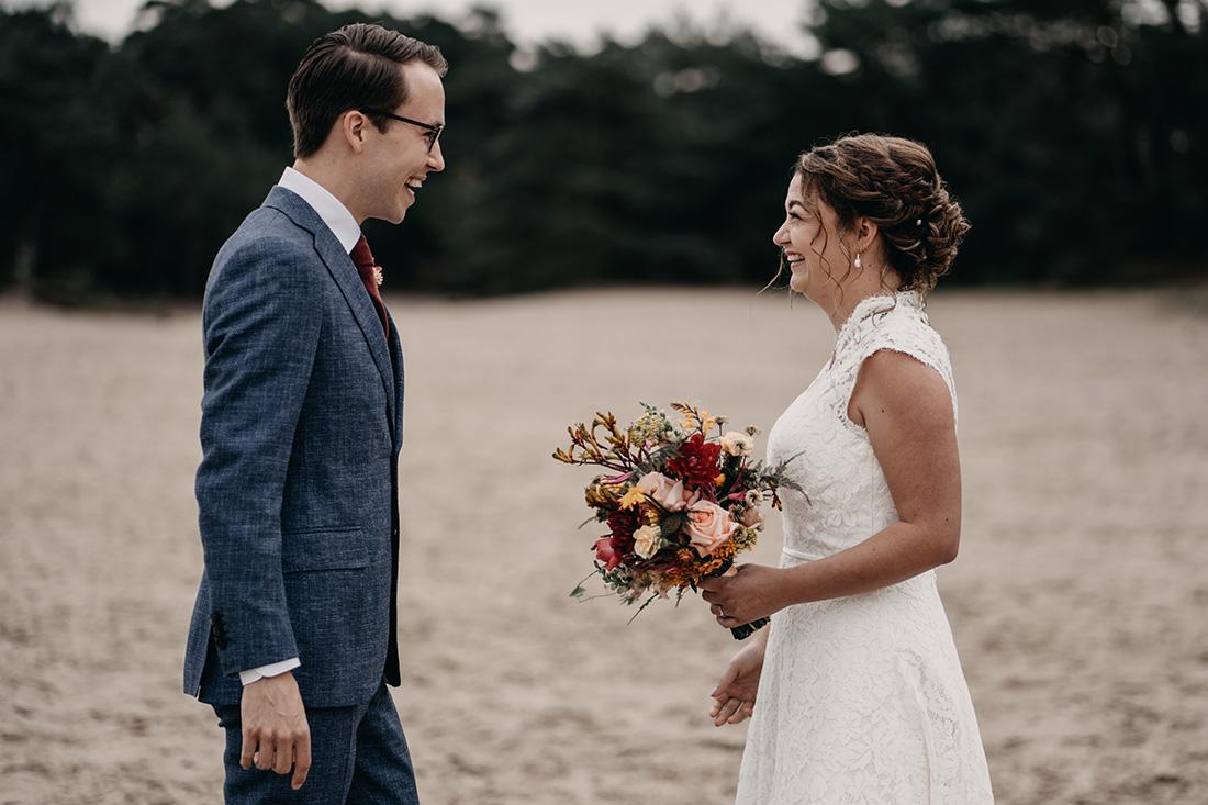 First look: bruid en bruidegom kijken lachend naar elkaar in natuur Soester Duinen