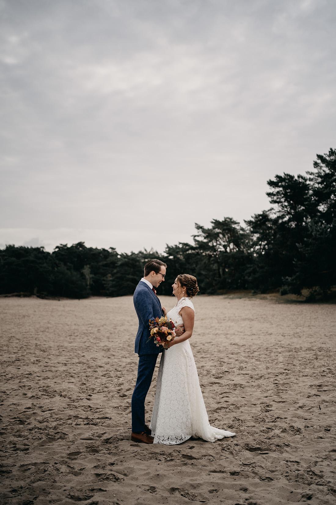 Bruid en bruidegom kijkend naar elkaar in natuur Soester Duinen