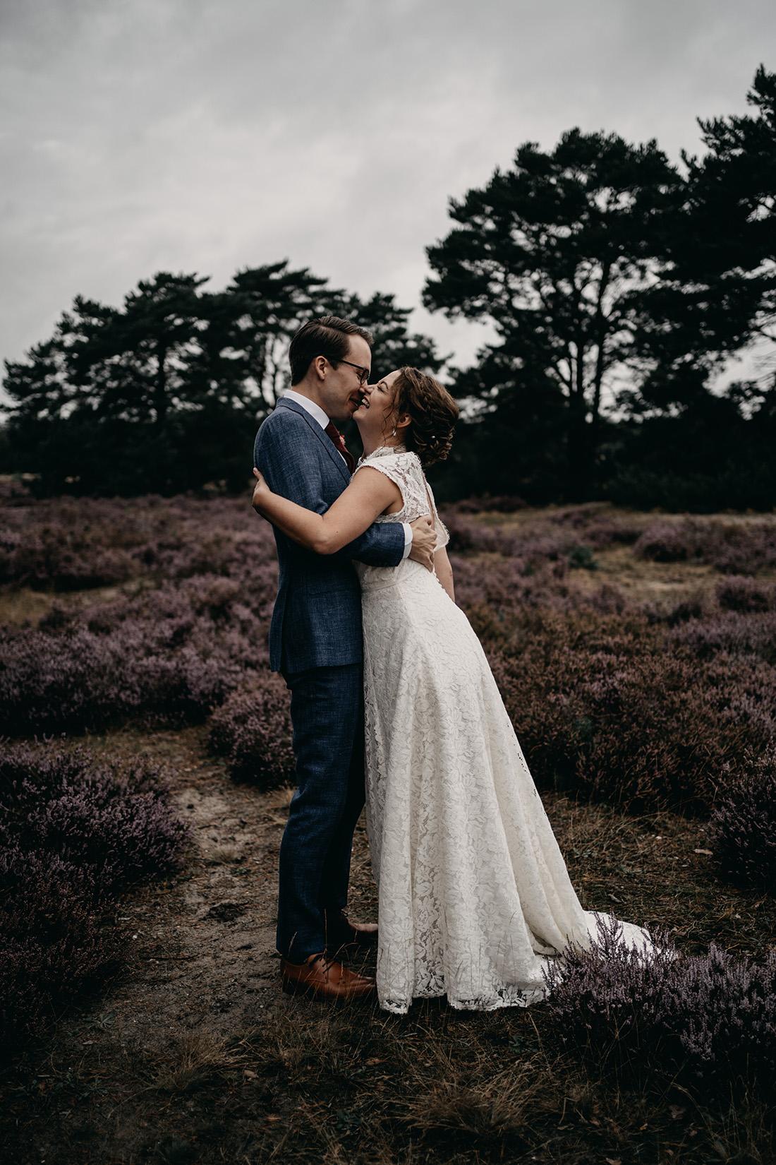 Kussende en lachende bruid en bruidegom in natuur Soester Duinen