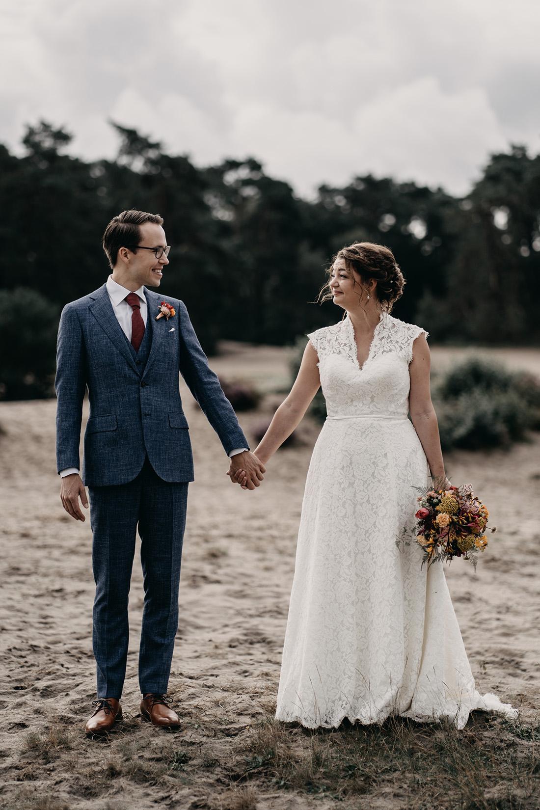 Bruidspaar houden elkaars handen vast in natuur Soester Duinen