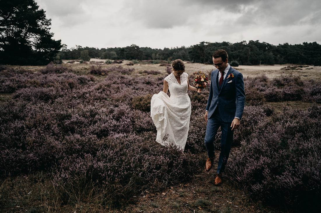 Bruidspaar loopt over heide in Soester Duinen