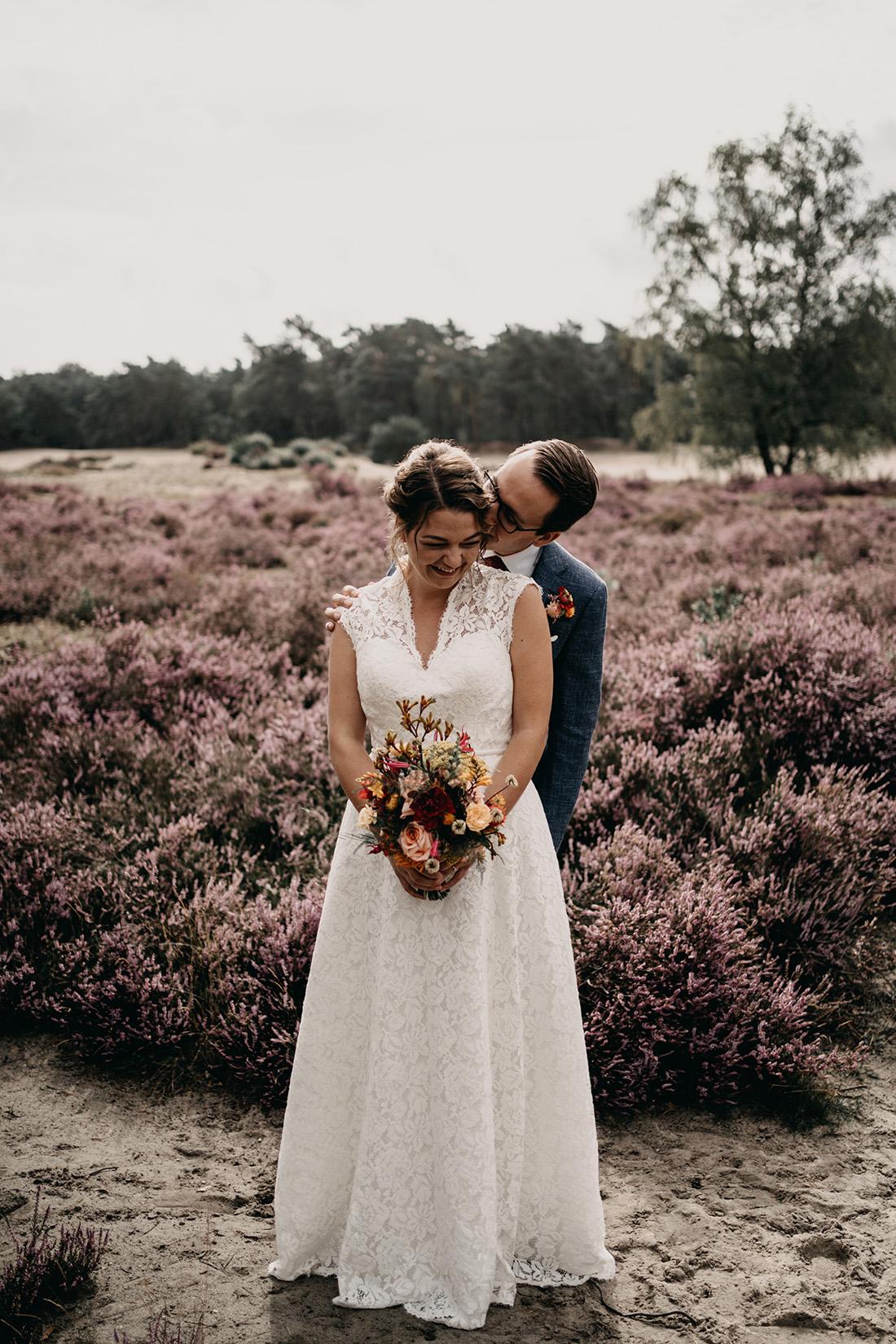 Bruidspaar op heide Soester Duinen, bruidegom kust bruid
