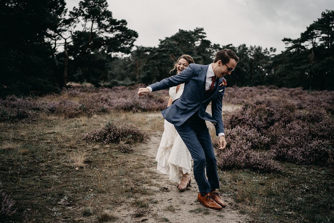 Bruidspaar heeft plezier en springen op en neer in natuur Soester Duinen