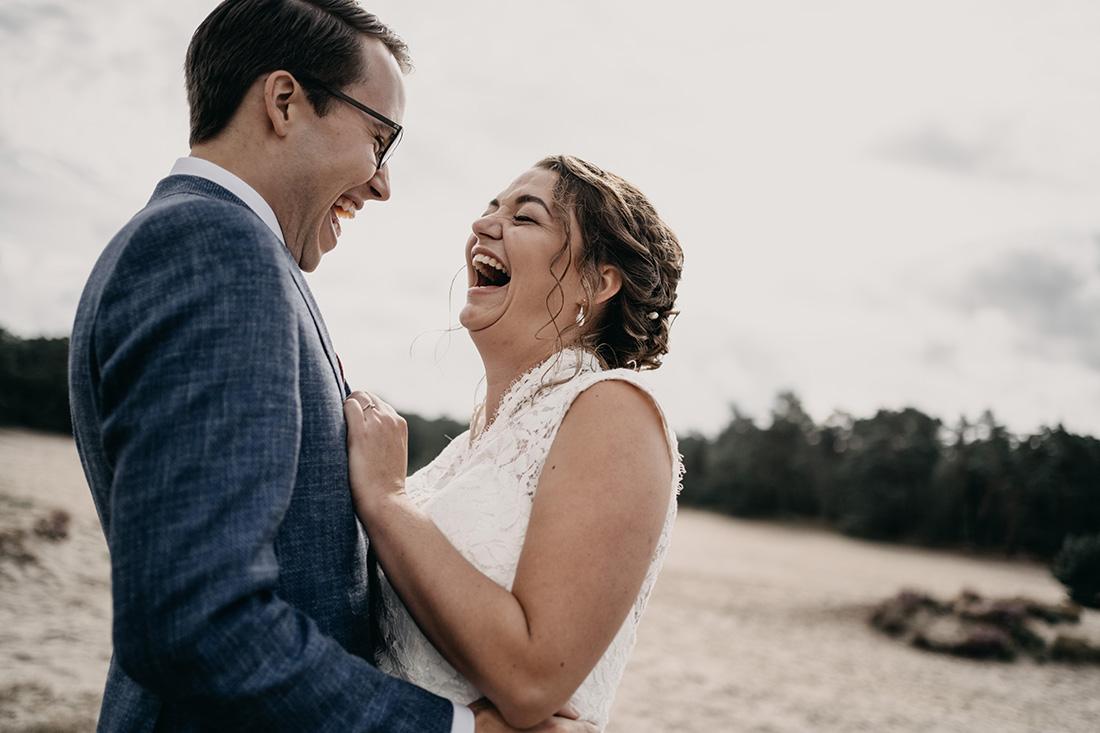Bruidspaar houd elkaar lachend vast in natuur Soester Duinen
