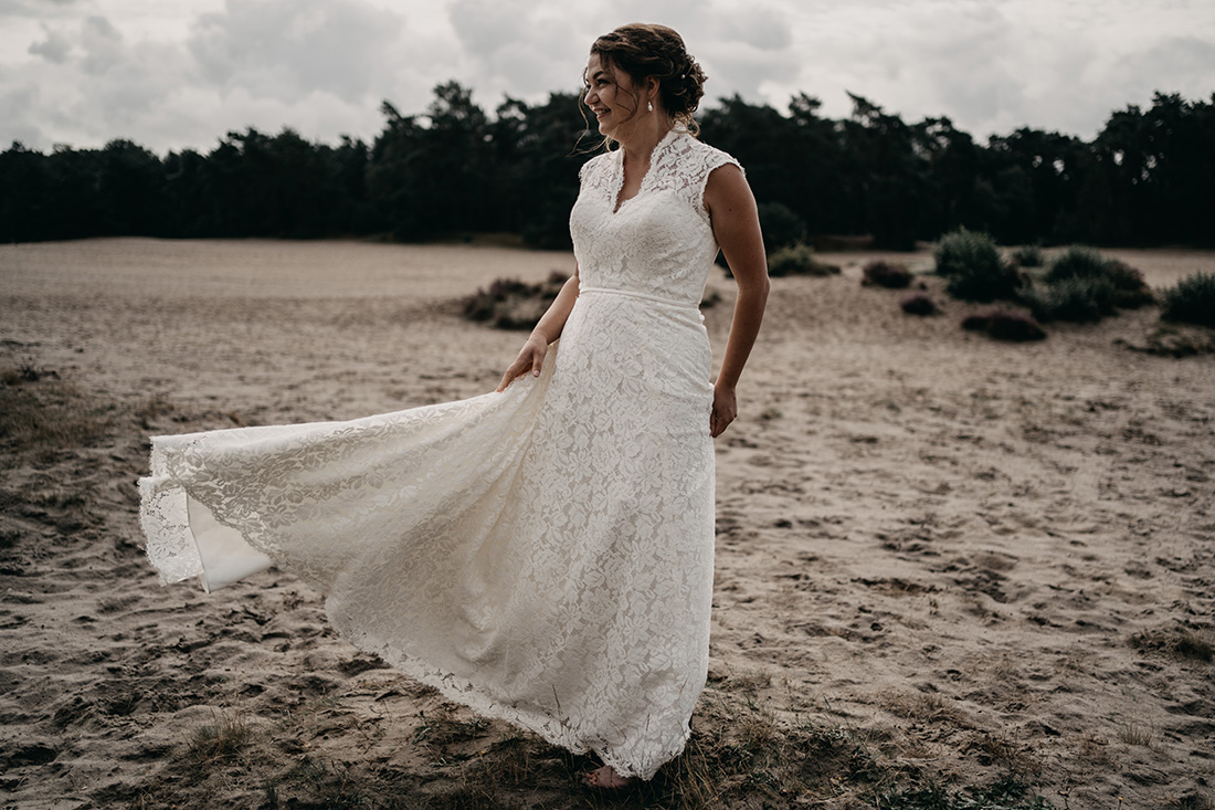 Jurk van bruid waait in de wind op zandvlakte Soester Duinen