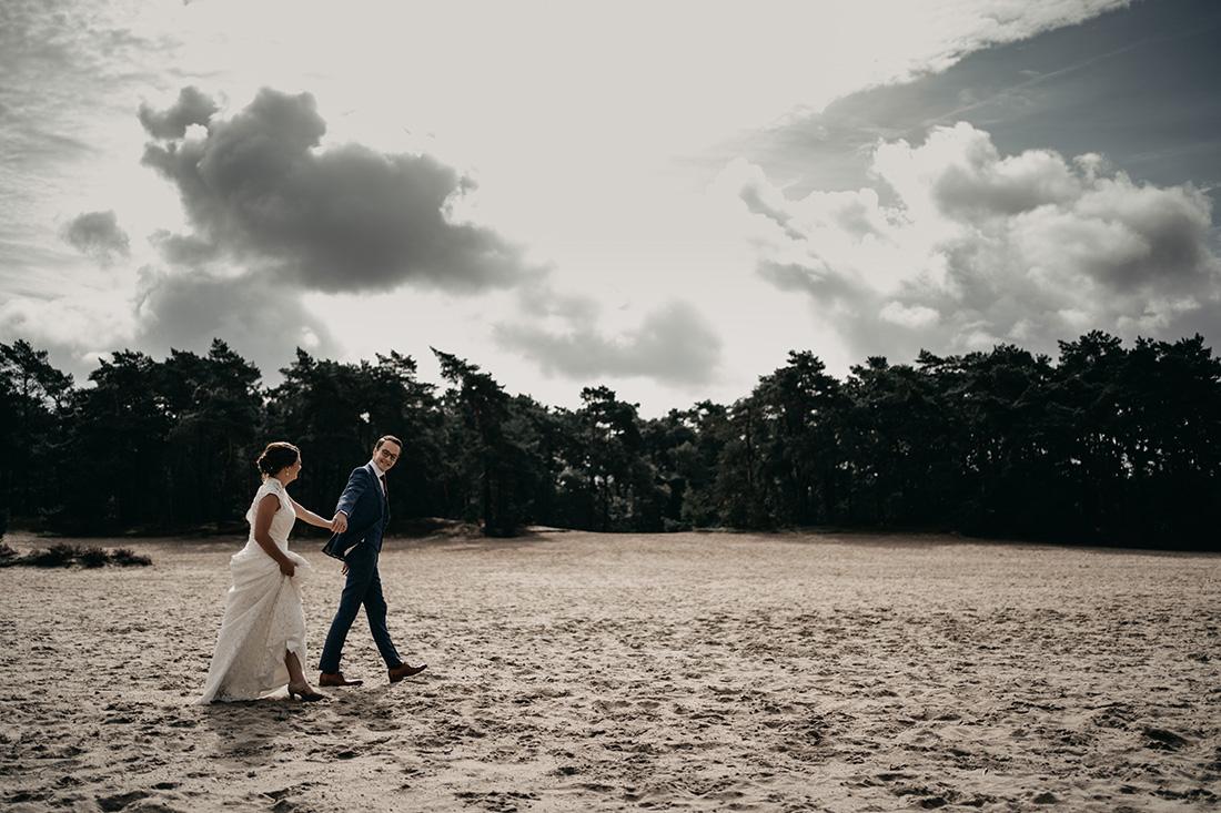 Bruidspaar loopt hand in hand over zandvlakte Soester Duinen