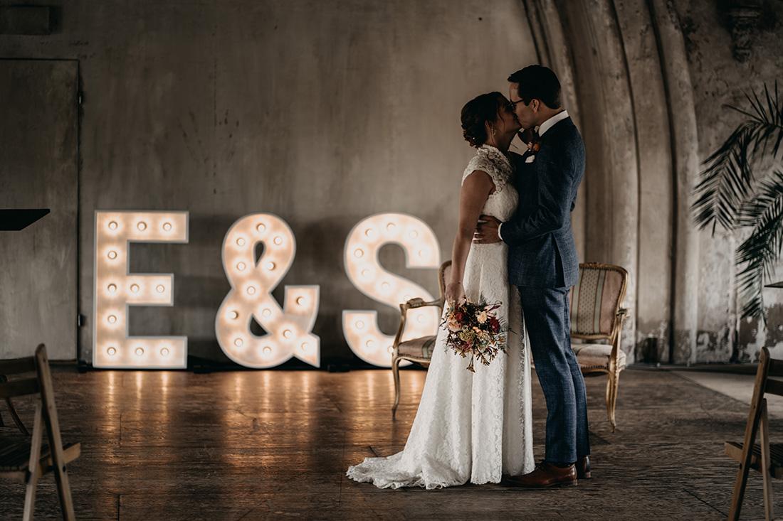 Bruidspaar kust elkaar voor lichtgevende letters in Metaal Kathedraal in Utrecht