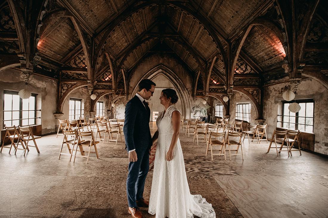 Bruidspaar kijkt naar elkaar in lege zaal in Metaal Kathedraal Utrecht