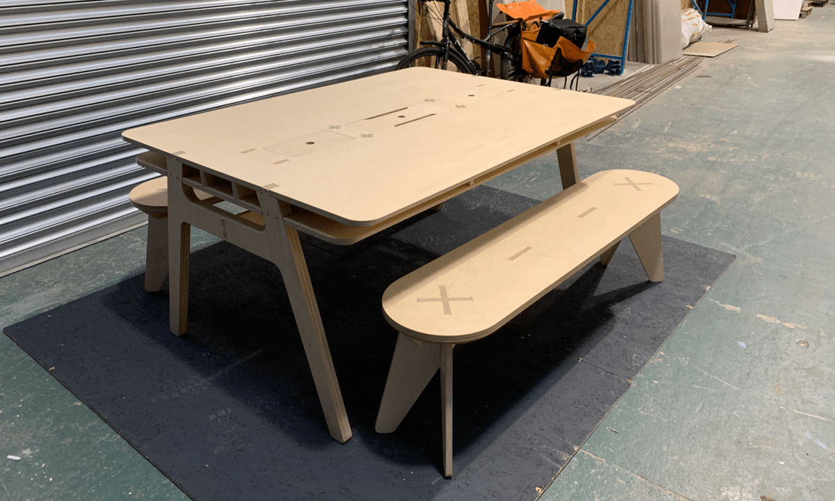 A plywood meeting table and 2 plywood benches in a workshop environment