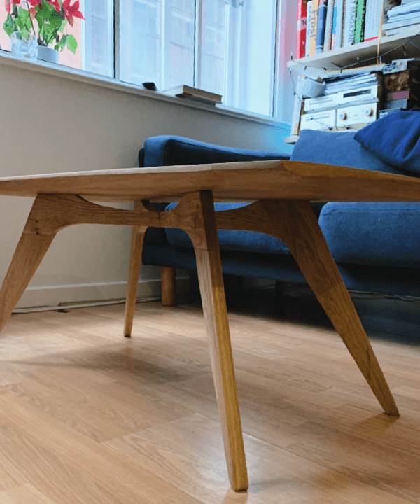 A solid oak mid-century style coffee table in a living room with a blue sofa