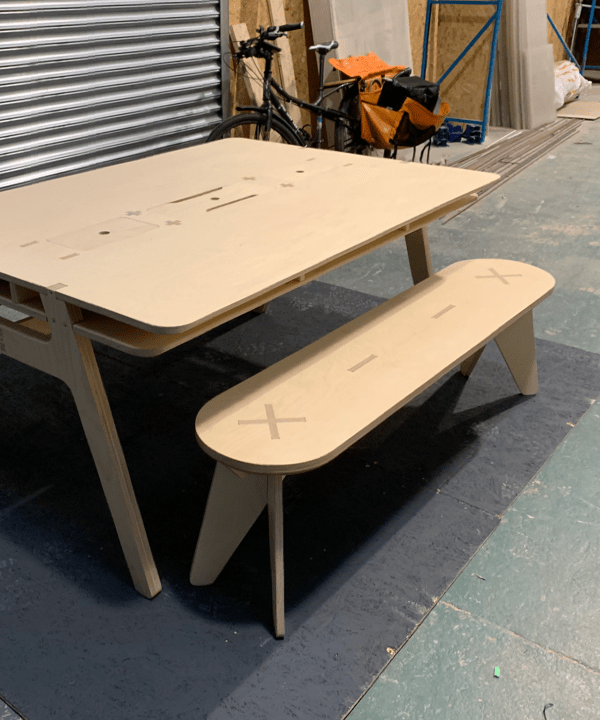 A plywood bench in front of a plywood table in a workshop environment