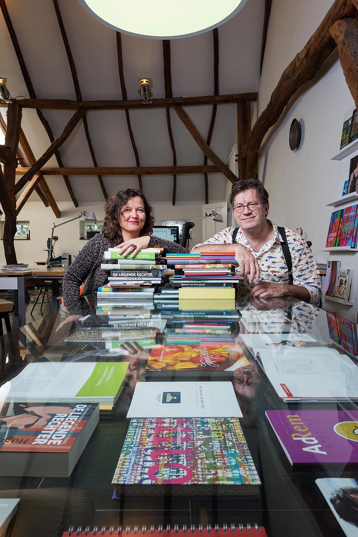 Marjorie en Godfried achter een stapel publicaties die ze hebben ontworpen