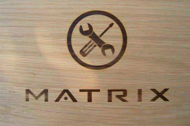 Het icoon 'service' (sleutel en schroevendraaier in cerkel) en het 'Matrix' logo met een brandstempel op een houten doos aangebracht.