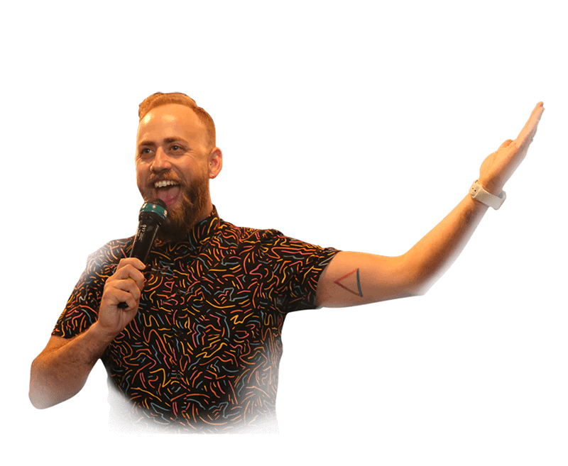Quiz Meisters host holding microphone. His name is Paul Wheeler. Wearing squiggly shirt. Triangle Tattoo.