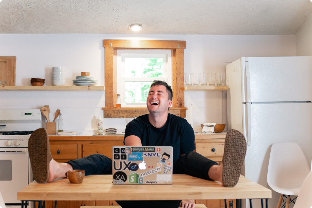 man with both legs up on a table in kitchen laughing