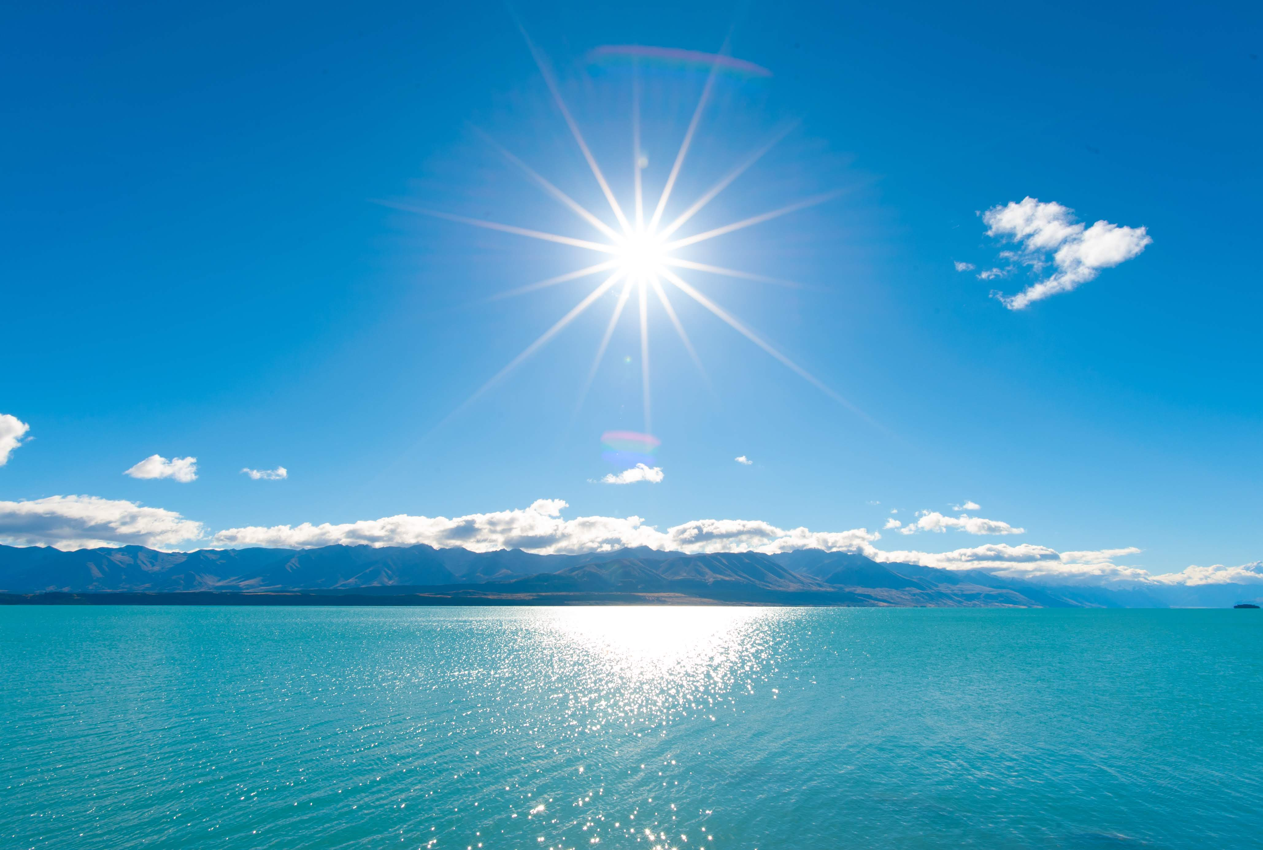 The sun reflecting on a blue lake