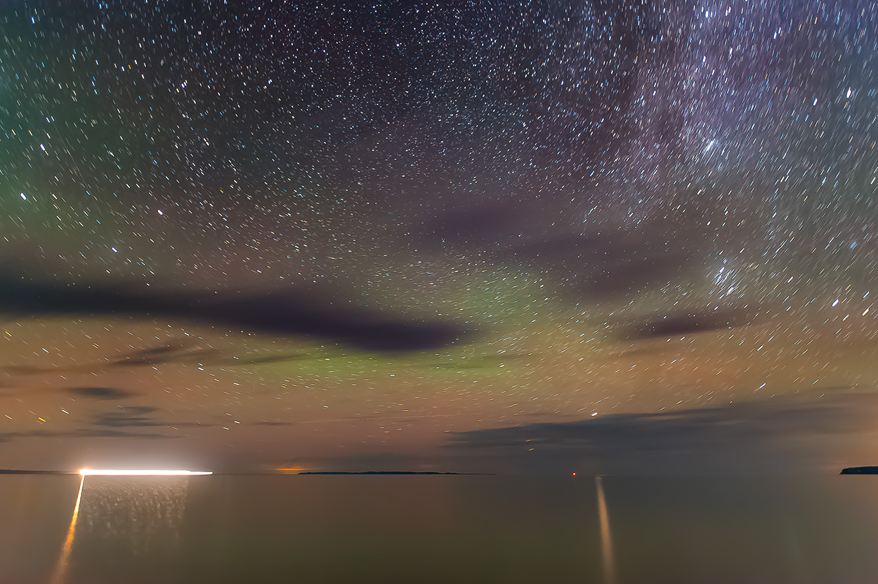A barge passing in Lake Michigan under a starry night sky