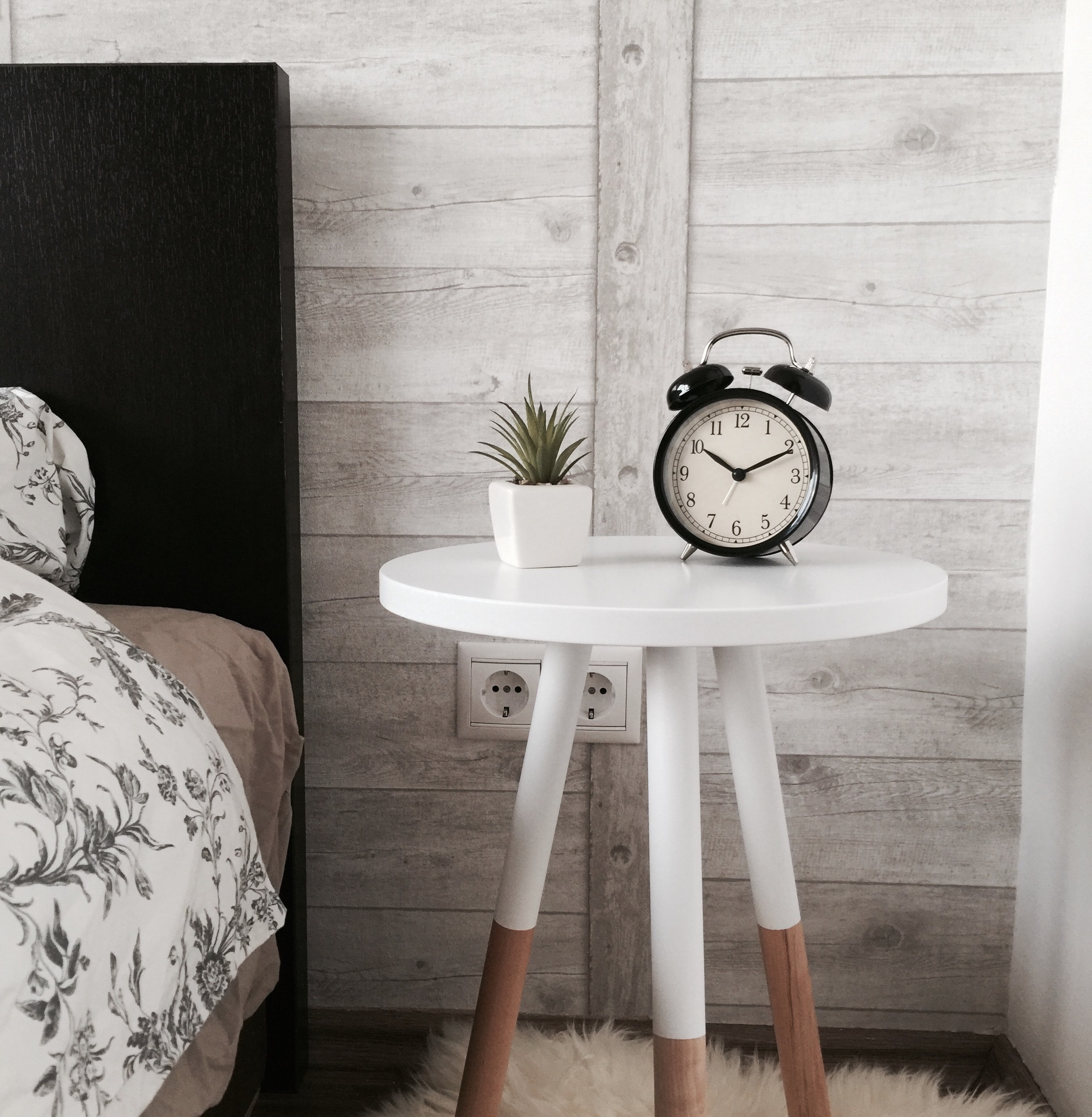 Alarm clock on a nightstand next to a bed