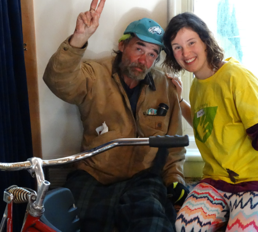 homeless man with a peace sign in thanks for the new bike he is receiving from kindista holiday free market 2015 with volunteer