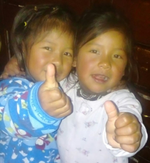 two little girls at the orphanage smiling and giving thumbs up