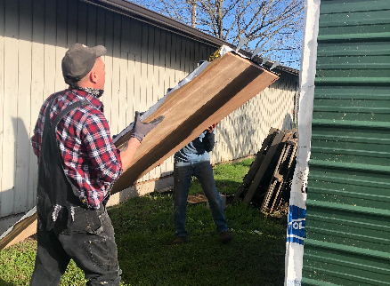 two men starting to lift a wall into place on a care shelter build