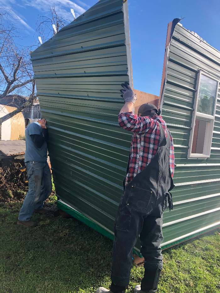 two men placing a wall on a care shelter build