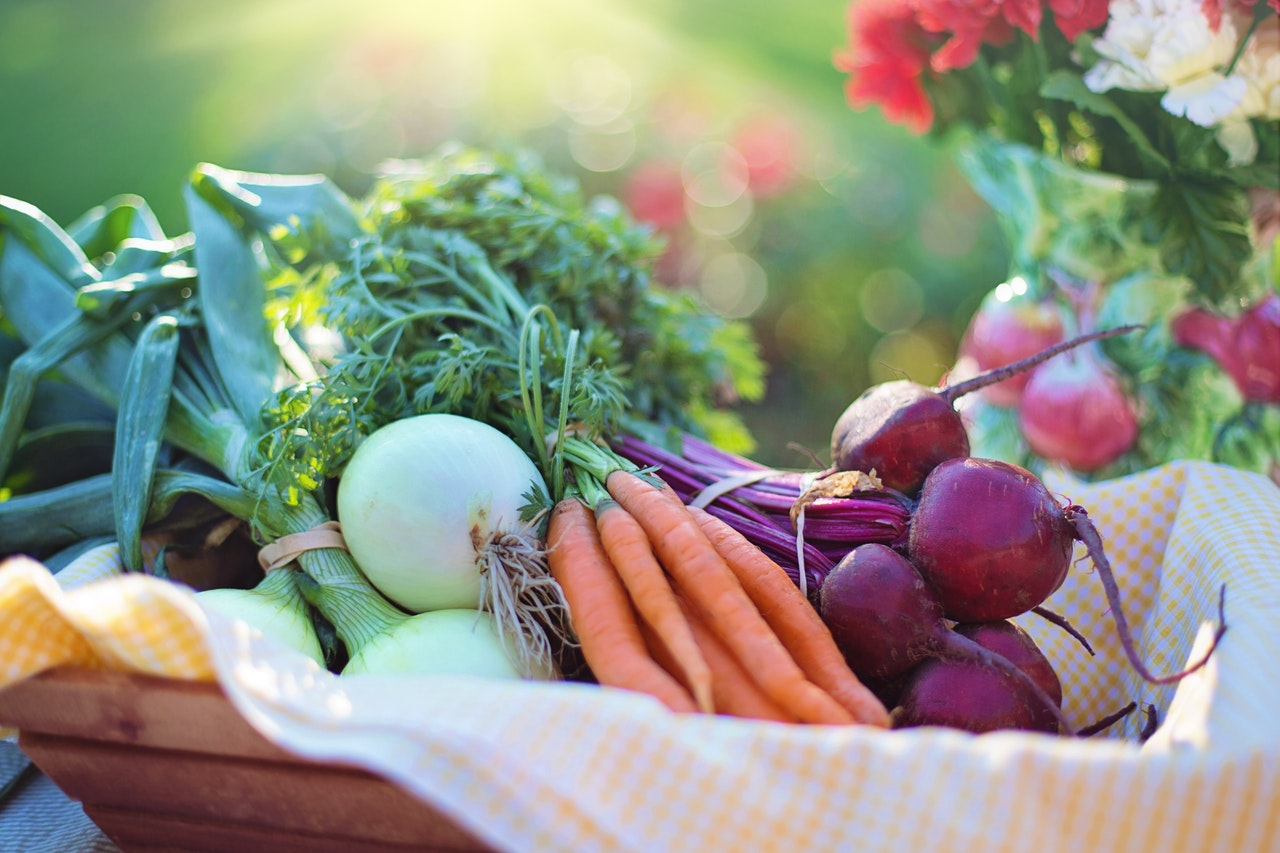 a veggie basket featuring carrots, onions and beets