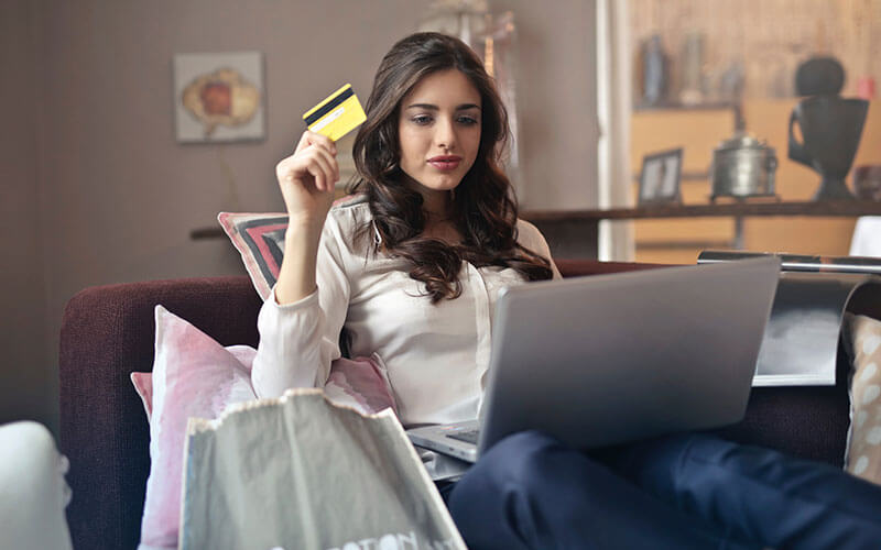 lady at her laptop holding a credit card making a purchase decision online