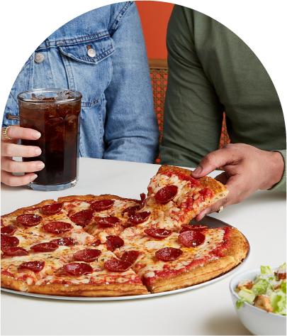 A couple sharing a slice of large thick crust pizza and a Caesar salad.