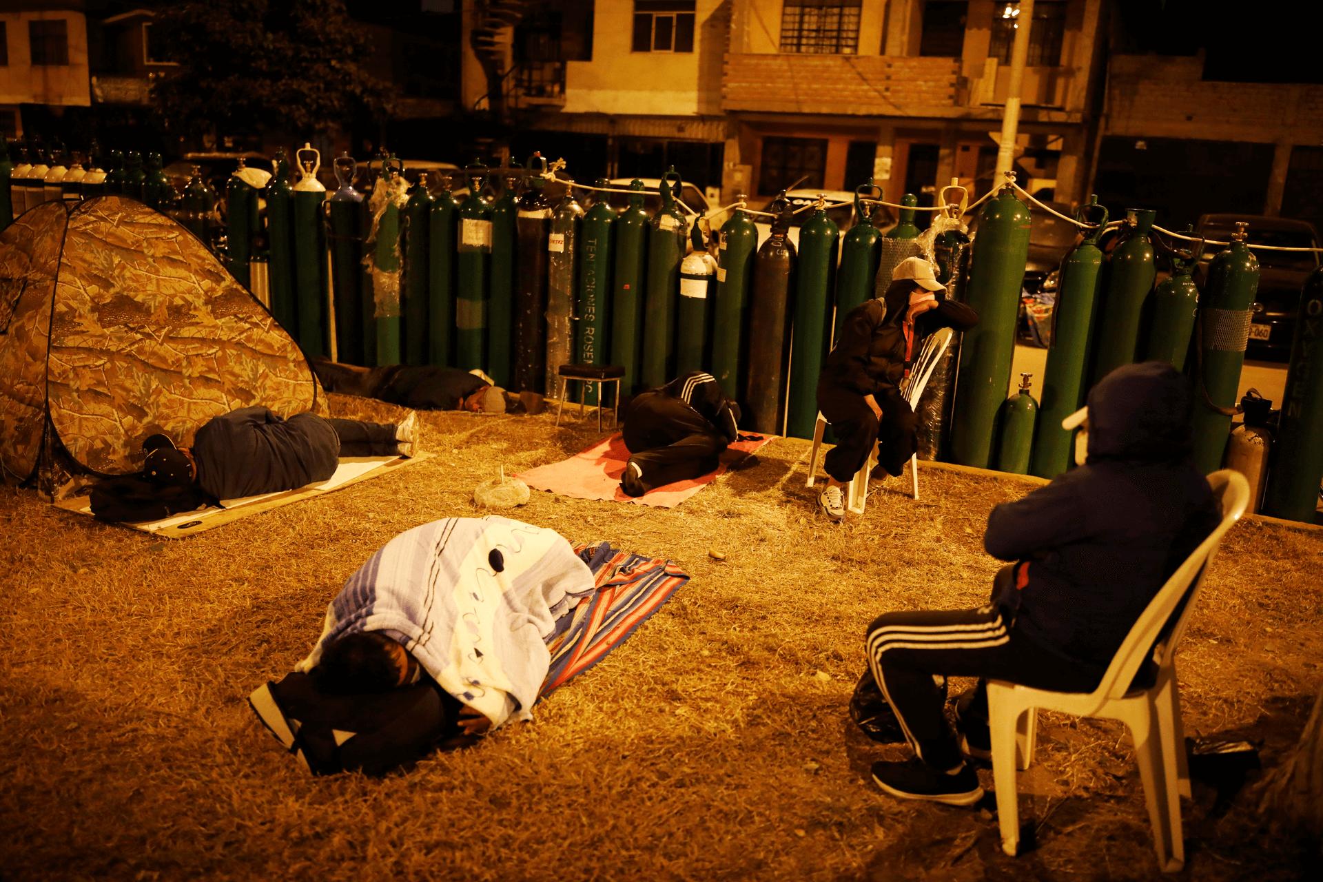 אנשים ישנים לצד בלוני חמצן ברחובות לימה בירת פרו, על מנת לשמור מקום בתור ליקיריהם. צילום: רויטרס