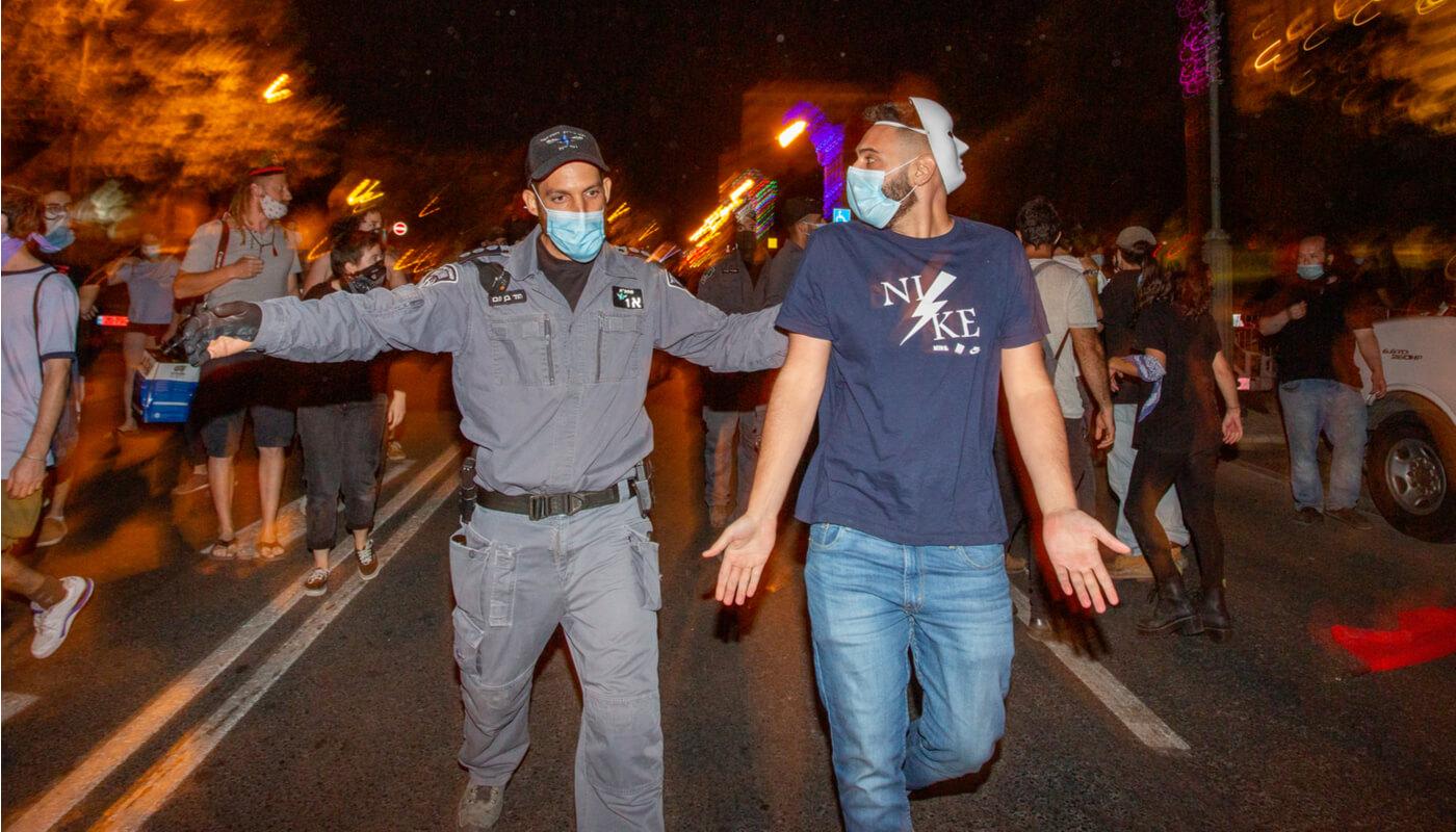 שוטר מפנה מפגין בירושלים בקיץ שעבר. צילום: שאטרסטוק