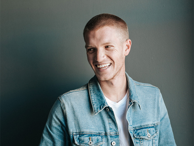 Image of a young male smiling and wearing a buzzcut, a jean jacket, and white tee shirt.