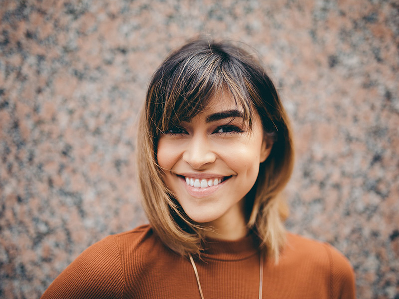 Picture of a 30 year-old women smiling and wearing a brown crew-neck