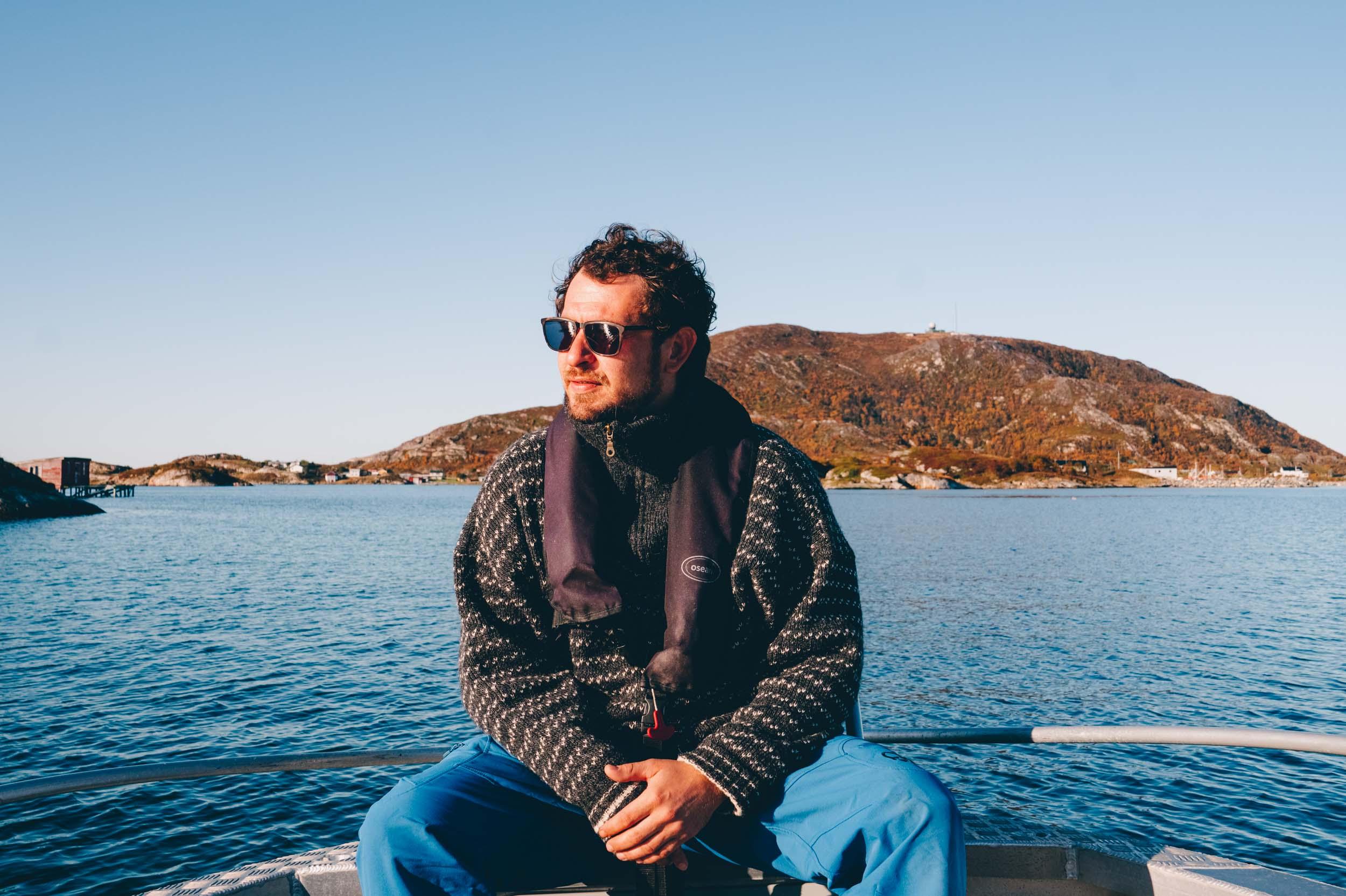 Mann med solbriller sitter i en båt på havet