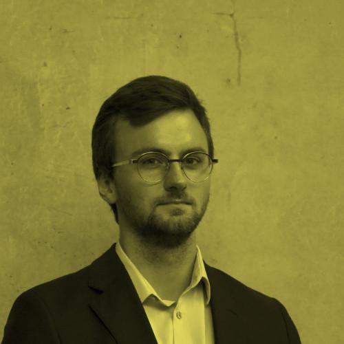 Młody elegancko wyglądający mężczyzna, około trzydziestego roku życia. Mężczyzna nosi modny model dużych, okrągłych okularów. Ubrany w strój oficjalny.