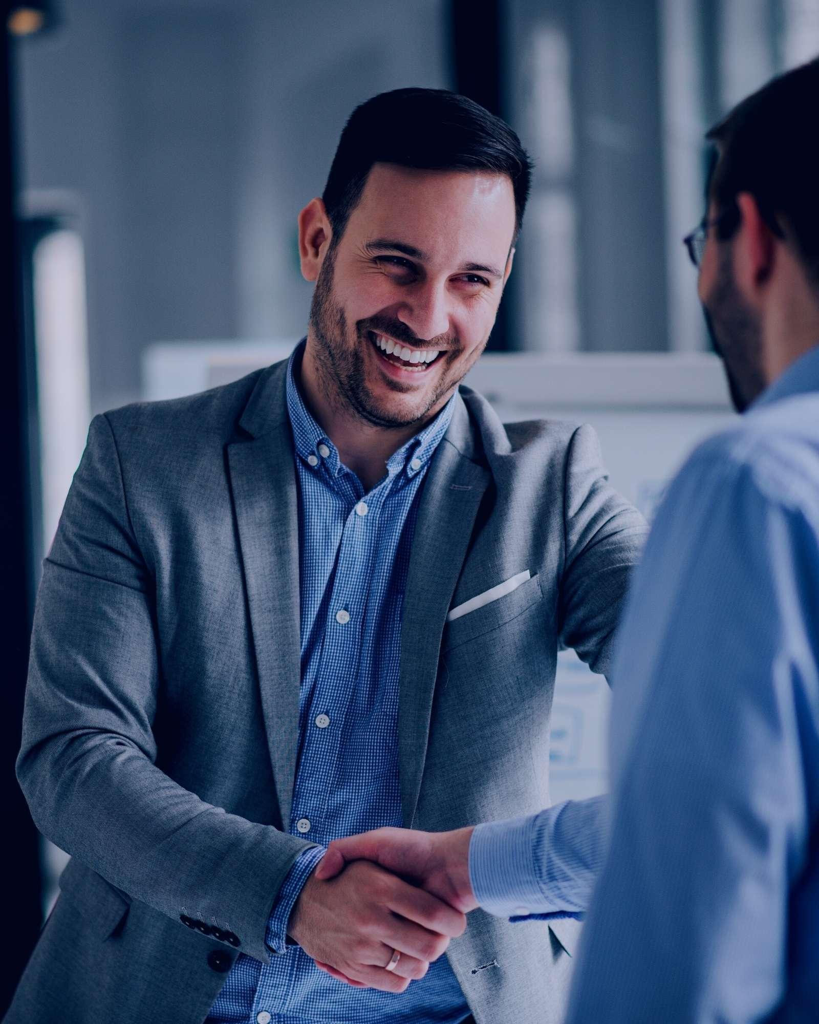 Portrait d'un manager serrant le main de manière enthousiaste avec un grand sourire