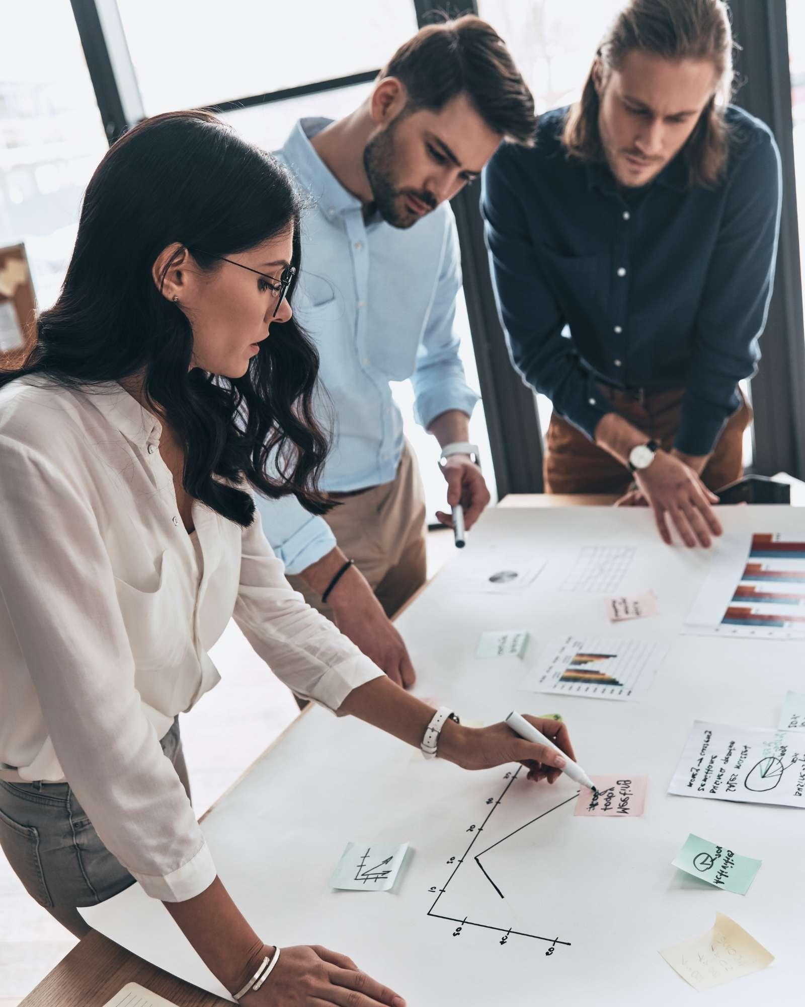 Moment de collaboration entre plusieurs collaborateurs autour d'un plan pour définir objectifs