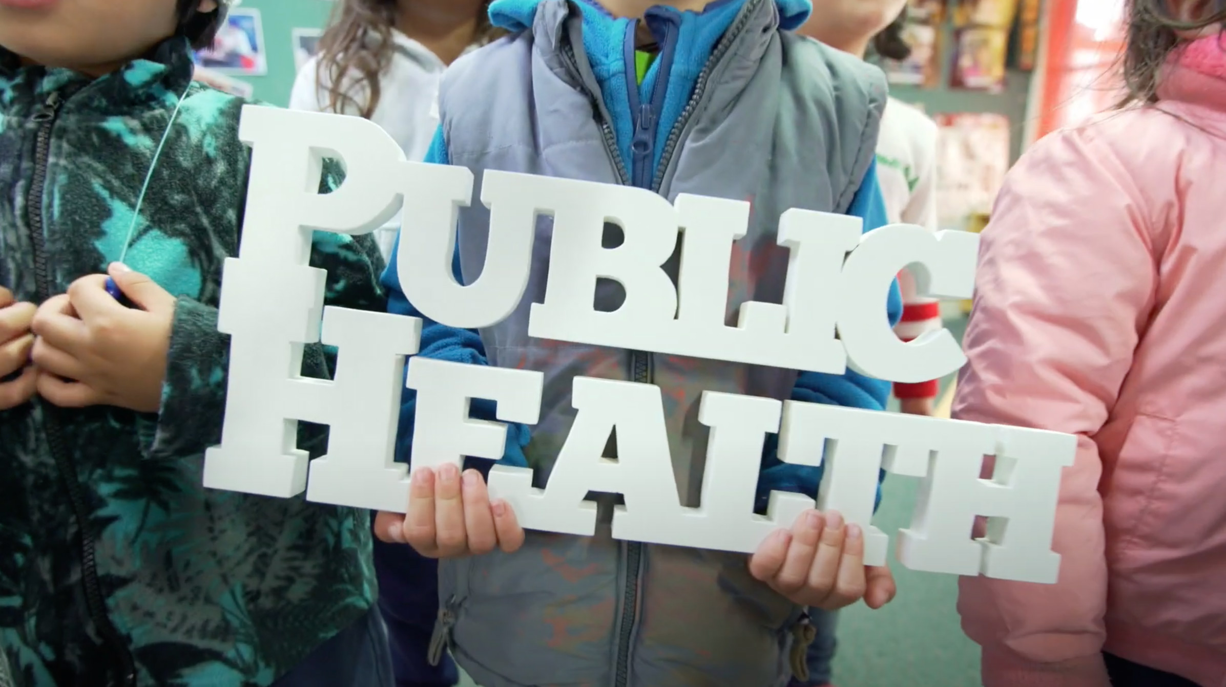 A group of children holding a sign that says public health