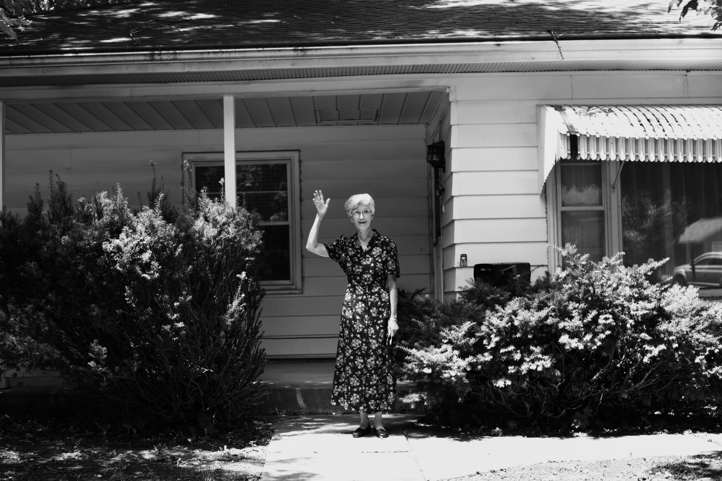 Jeanne standing in front of her house waving