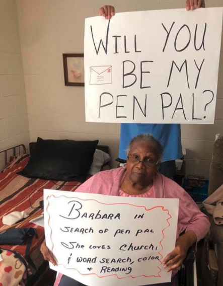 """a nursing home resident holds a sign saying """"will you be my pen pal?"""""""