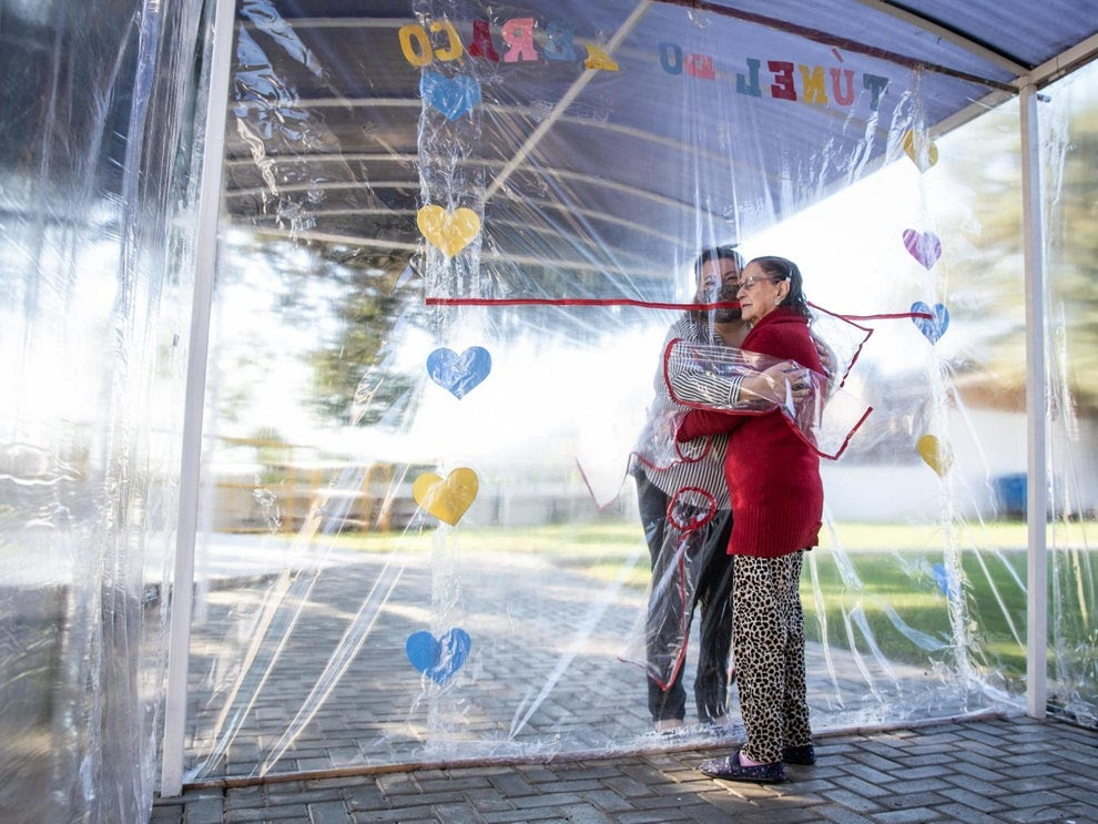 a nursing home resident and her family member hug through a plastic curtain